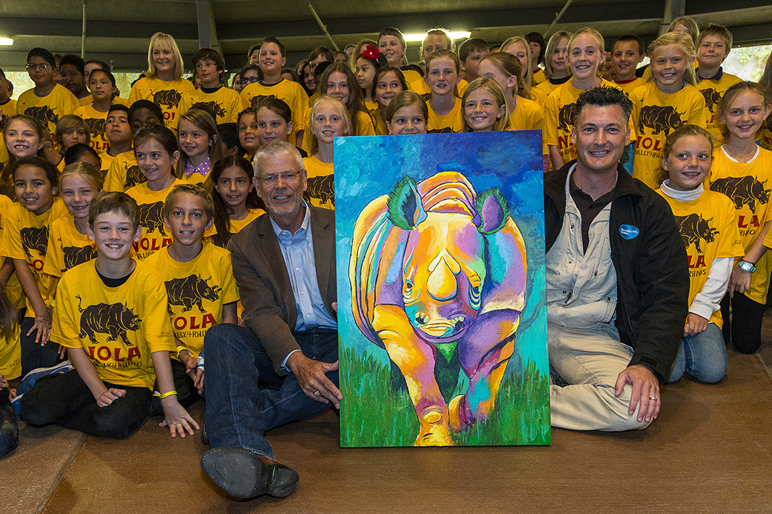 "Students from San Pasqual Union Elementary School, William C. Woody, Chief of Law Enforcement, U.S. Fish and Wildlife Services (left of painting) and Rick Schwartz, San Diego Zoo Global ambassador, (right of painting) were among those who celebrated Endangered Species Day at the San Diego Zoo Safari Park at a special ""Rally 4 Rhinos."" The group posed with a painting of a rhino created by the students and presented to the U.S. Fish and Wildlife chief as a token of their appreciation for the work he and his department does for endangered species. 	The Safari Park's Rally 4 Rhinos was held to raise awareness of the plight of rhinos in the wild and the urgent need to protect these iconic endangered species for future generations. Event attendees included government officials, school students, celebrities, San Diego Zoo Global personnel and Safari Park guests.  There are five species of rhinos – black, white, greater one-horned, Sumatran and Javan. With all species together, there are less than 30,000 rhinos worldwide. Rhinos are facing the worst poaching crisis in history, with an average of three rhinos a day being killed in South Africa. At the current poaching rate, rhinos could become extinct in 15 years. Rhinos are poached for their horns, which are made of keratin, the same thing as human fingernails and hair.  	 Photo taken on May 15 by Ken Bohn, San Diego Zoo Safari Park."